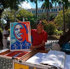 vendedor en la plaza de armas sosteniendo un cartel publicitario de la visita de Obama a la Habana