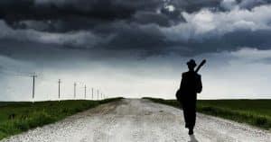 guitar player silhouette walking on desert street