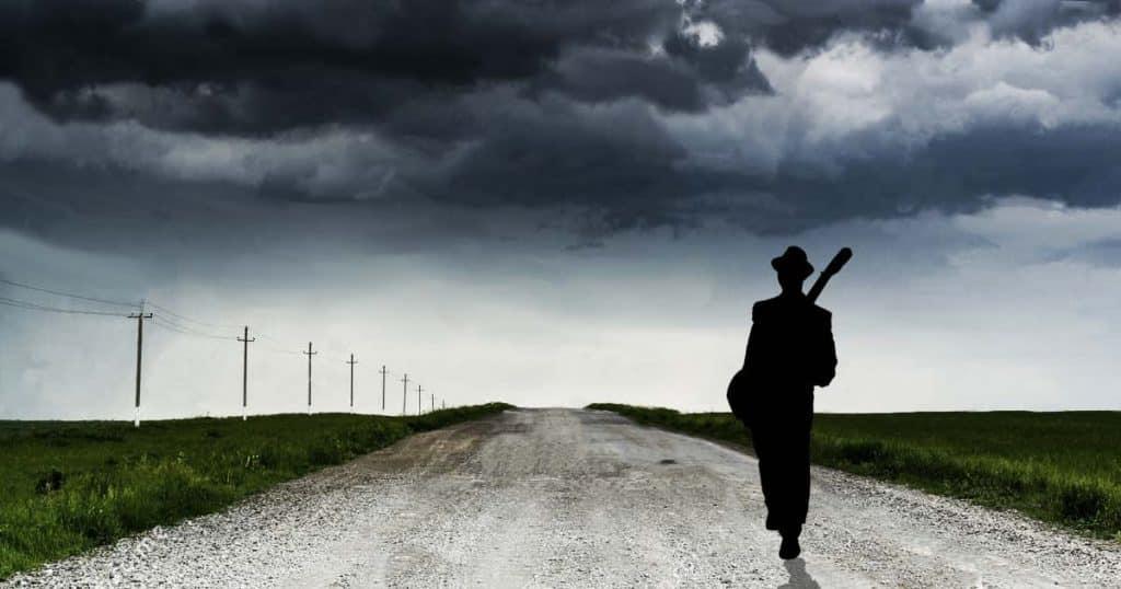 silueta de un hombre con guitarra al hombro caminando por una carretera desolada