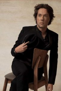 Rufus Wainwright sit in a chair and with a hat in his hand