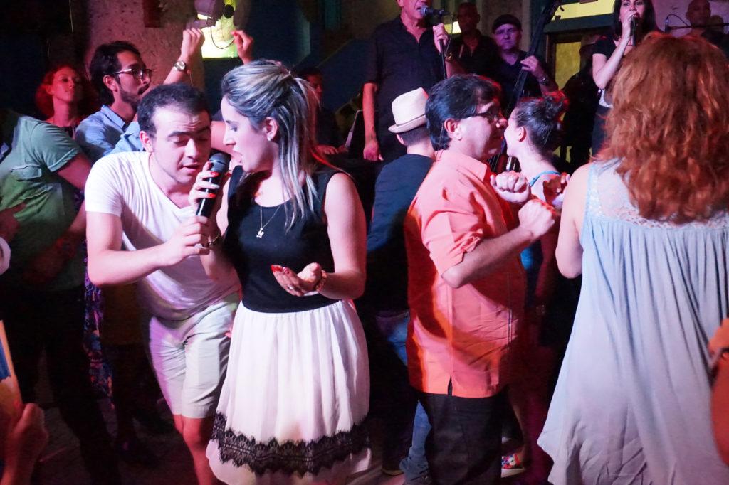 Joven cantante cubana del proyecto #tradicionalesdelos50 en un night club y personas bailando