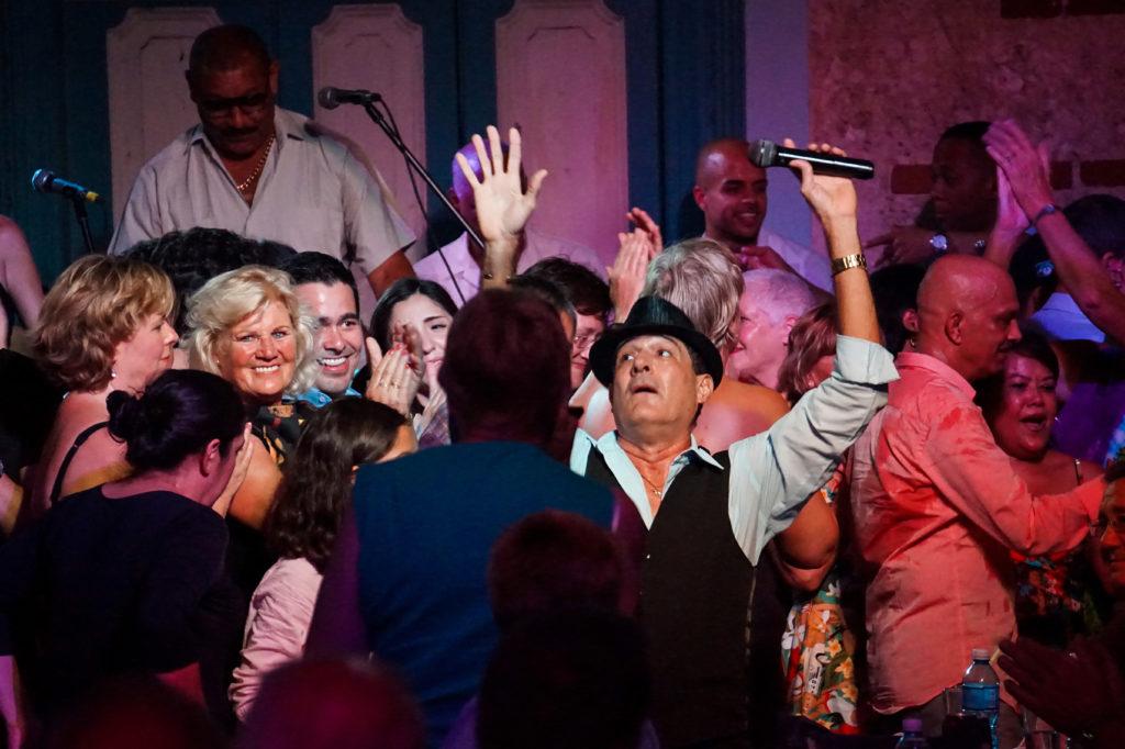 Gente alegre y sonero cubano actuando en vivo en un lugar para bailar y escuchar música cubana