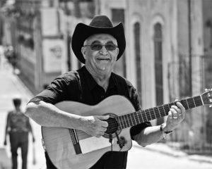 eliades ochoa con guitarra en una calle