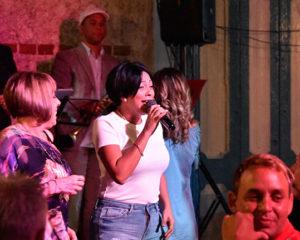 arlenis rodriguez lazo con micrófono en la mano y cantando